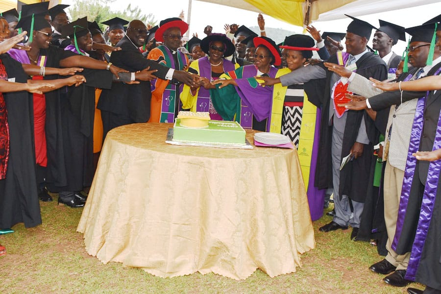 Hon Mary Karoro Okurut, Minister of General Duties, Office of the Prime Minister cuts the cake with Graduands at the MIHS graduation